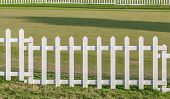 foto of farm land  - White wooden fence in farm field marks for land property - JPG