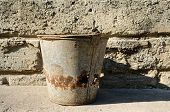 old bucket on background of a cement wall