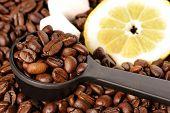 Coffee grains in a measuring spoon lemon and sugar