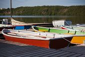 Color Wooden Boats With Paddles In A Lake