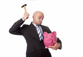 foto of spanish money  - bald Hispanic businessman with hammer in his hand holding pink piggybank ready to break the piggy bank and take money and savings out isolated on white background - JPG