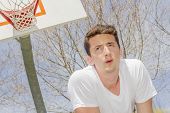 picture of basketball  - Basketball player taking a breather on outdoor basketball court - JPG