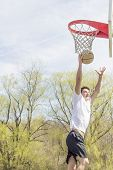 picture of leaping  - Young man doing basketball trick shots as he leaps through the air
