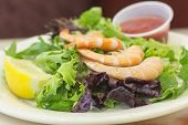 picture of shrimp  - Shrimp cocktail salad with legs on shrimp and lemon wedge