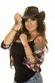 stock photo of cowgirl  - a cowgirl with her hand on her hat and with her plaid shirt falling off of her shoulder showing her tattoo - JPG