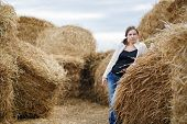 stock photo of haystack  - Pretty young woman in a white blouse and jeans posing on the background of haystacks - JPG