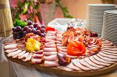 stock photo of smoked ham  - Choice of smoked ham and sausages on the table - JPG