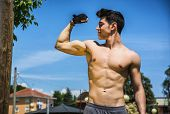 stock photo of shirtless  - Shirtless handsome fit athletic young man doing bicep pose outdoor - JPG