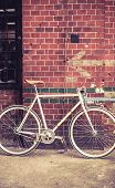 stock photo of commutator  - City bicycle fixed gear and red brick wall vintage bike - JPG