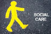 pic of pedestrians  - Yellow pedestrian figure on the road walking towards SOCIAL CARE - JPG