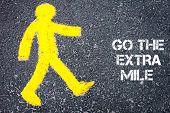 picture of mile  - Yellow pedestrian figure on the road walking towards GO THE EXTRA MILE - JPG