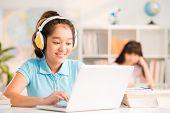 image of schoolgirl  - Vietnamese schoolgirl with headphones using laptop in the class - JPG