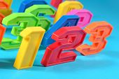 picture of blue things  - Colorful plastic numbers 123 close up on a blue background - JPG