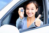stock photo of thumb  - Happy girl in a car showing a key and thumb up gesture