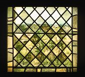 foto of pigment  - An old stained glass window with pigmented window panes and leaded glass distorts the French countryside into a a view that looks like an impressionist painting - JPG