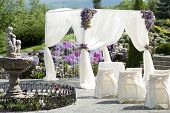 foto of marriage decoration  - Festive wedding ceremony decoration of lightweight white fabric and fountain on purple violet and gtreen natural background horizontal picture - JPG