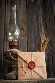 stock photo of revelation  - love letter and an old oil lamp on a wooden background - JPG