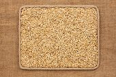 image of sackcloth  - Frame made of rope with oats grains on sackcloth as background texture - JPG