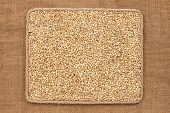 picture of sackcloth  - Frame made of rope with pearl barley grains on sackcloth as background texture - JPG