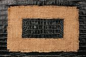 picture of crocodiles  - Frame of burlap lies on a background of crocodile leather with place for your text - JPG