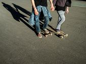 foto of skate board  - Happy couple on a longboard skate together on the boards holding hands - JPG
