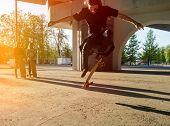 stock photo of skateboarding  - Silhouette skateboarder jumping in city on skateboard under the bridge - JPG