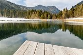 pic of pier a lake  - This photo shows a general landscape view of lake and mountains from the wooden pier - JPG