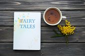 image of mimosa  - Fairy Tales book with cup of tea and sprig of mimosa on wooden background - JPG