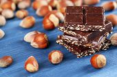 pic of hazelnut  - Pieces of chocolate with hazelnut on wooden table - JPG