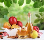 image of cider apples  - Apple cider in bottle with cinnamon sticks and fresh apples on nature background - JPG
