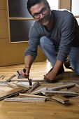 stock photo of leak  - Vertical image of a worker disassembling wooden floor ruined from moisture and water leak - JPG