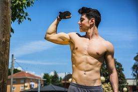 picture of bicep  - Shirtless handsome fit athletic young man doing bicep pose outdoor - JPG