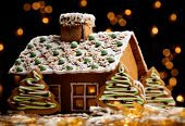 stock photo of gingerbread house  - Gingerbread house with lights inside dark background - JPG