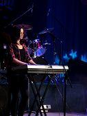 Girl playing on a keyboard on a concert in the spotlight. Dark blue lighting.