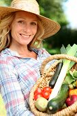 Woman with a straw hat holding basket of vegetables.