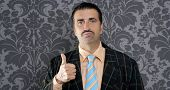 nerd businessman gesturing ok positive with hand over retro wallpaper