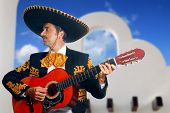Charro Mariachi singer playing guitar in Mexico with white house background