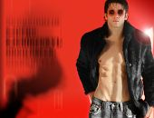 Fashion portrait of edgy male model wearing eye makeup in fur against red background