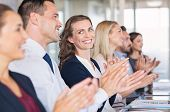 Businessmen and business women sitting in a row and applauding at meeting. Successful businesspeople poster