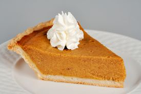 pic of pumpkin pie  - A slice of pumpkin pie topped with a dapple of whipped cream - JPG