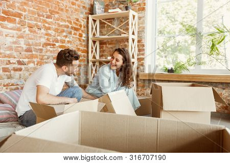 poster of Young Couple Moved To A New House Or Apartment. Unpacking Cardboard Boxes Together, Having Fun At Mo