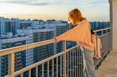 Tween Redhead Girl In Pullover, Jeans And Sunglasses Standing On Balcony Against High-rise Multi-sto poster
