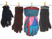 A Variety Of Gloves Hanging On A Rope, Isolated On A White Background.