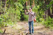 Man Hiker Taking Photo Smart Phone In Forest. Attractive Traveler Making Photo With Mobile Phone. Tr poster