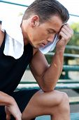 picture of bleachers  - Portrait of a young athletic man with workout towel sitting on the bleachers - JPG