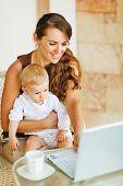 Trabalho de jovem mãe com bebê no Laptop