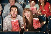 stock photo of bleachers  - Group of frightened people watching movie spill popcorn - JPG