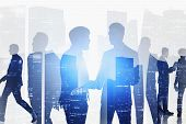 Silhouettes Of Business People Shaking Hands And Cooperating In Modern City. Concept Of Teamwork And poster