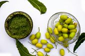 Neem Paste Or Nim Paste In A Glass Bowl Isolated On White Along With Neem Fruit In Another Bowl And poster
