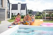 Happy Family Chilling Near The Pool On Hot Summer Day poster